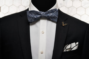 An image of a mannequin dressed in the Pratt navy patterned bow tie and combining the vintage gold stag lapel pin and white pocket square.