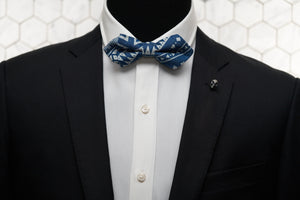 A mannequin is shown wearing our Heisser Triangle  denim bow tie with gold skull lapel pin.