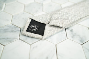 The DM hexagonal logo is shown stitched on the back of the creme men's linen skinny tie by Dear Martian.