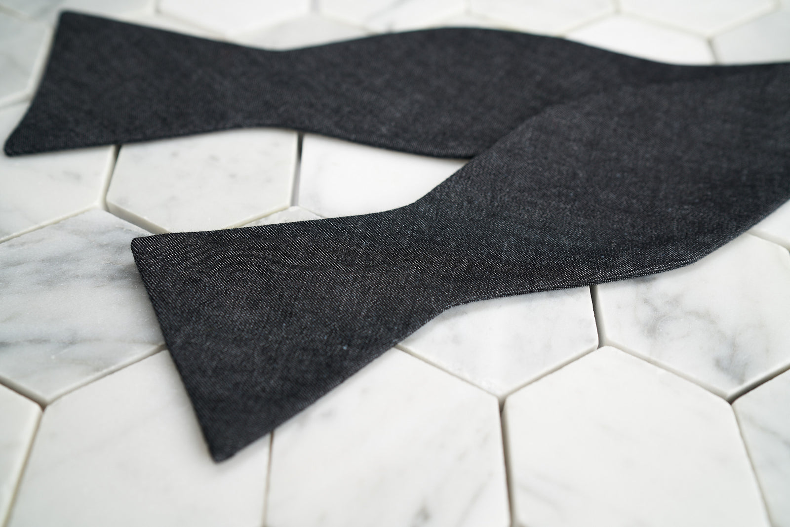 An image of Dear Martian's denim black bow tie untied, lying against a hex tiled background.