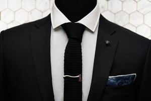 The Dear Martian, jet black tie is displayed on a mannequin, which features men's accessories such as the blue rose denim pocket square, silver axe tie clip, and skull lapel pin.