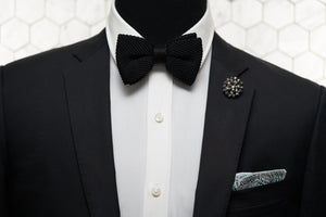 A mannequin donning a black suit jacket with Dear Martian accessories; our signature Crow Hill jet black pre-tied bow tie, Cranford rose denim pocket square, and Notorious copper beaded lapel pin.