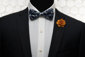 A model wearing Dear Martian, products which include a camo novelty bow tie and orange flower lapel pin.