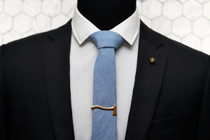 Featured on a mannequin lies the Dear Martian, Aqua Blue Chambray tie with mens acessories; our Kloven gold axe Tie Clip and Vie gold Skull Lapel Pin