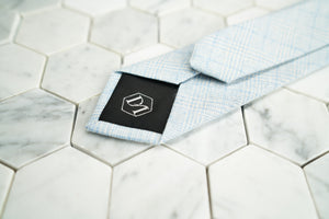 An image of the back of Dear Martian's light blue plaid skinny tie, which features the exclusive hexagon DM logo.