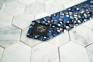 The back of the navy dotted skinny tie by Dear Martian, features a stitched DM hexagonal logo.
