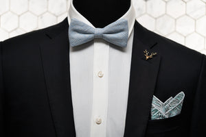 A dapper mannequin dressed in a black suit jacket with Dear Martian accessories, which include; the sky blue plaid bow tie, gold stag lapel pin, and the Whitman pocket square.