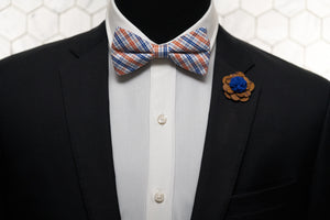 An image of a dandy mannequin dressed in a Dear Martian wooden lapel pin a summer plaid bow tie.