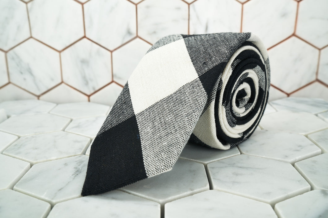 The Bobby Fischer monochrome argyle linen necktie from Dear Martian, is rolled and sitting on a hexagonal background.