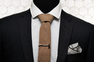 The Dear Martian brown linen tie is paired with a silver ax tie clip and Lexington white pocket square; which are featured on a mannequin wearing a black men's blazer.
