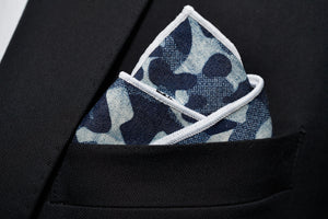 A blue camo denim pocket square by Dear Martian, Brooklyn is shown folded on a black suit pocket.