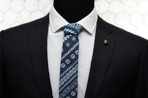 Our Dear Martian, handmade denim skull patterned tie is displayed on a mannequin featuring our Vie gold skull lapel pin.