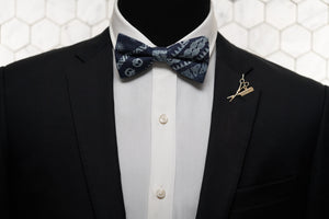 An image of a mannequin in a black suit dressed with a denim blue celtic patterned bow tie, which is paired with the Fleet St. gold lapel pin by Dear Martian, Brooklyn.