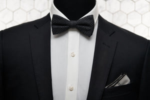 An image of a mannequin dressed in a Parisian inspired look with a charcoal grey bow tie and white argyle linen pocket square.