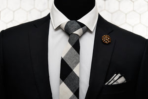 A black and white checkered tie is displayed on a mannequin. The mannequin is also wearing a black suit, Dear Martian's beaded copper lapel pin, and a black and white striped pocket square.