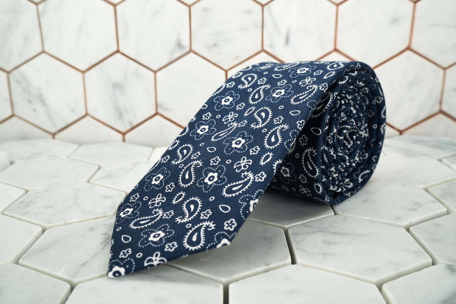 A paisley navy patterned necktie by Dear Martian, is named the Cowboy and rolled up against a white background.