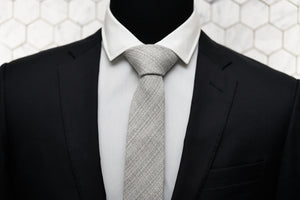 The Barclays Dear Martian neck tie is knotted and displayed on a mannequin wearing a black suit jacket and white button down.
