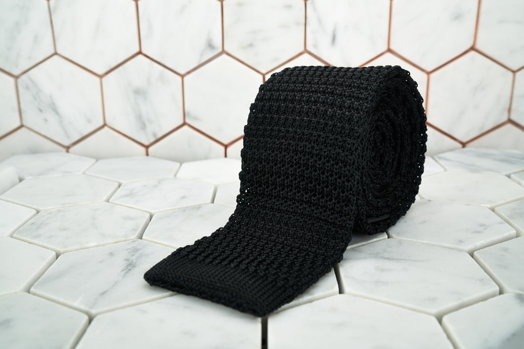 This is the Dear Martian sleek jet black, silk knitted neck tie rolled and displayed against a hexagon background.