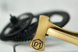 A detailed image of the back of the antique brass axe tie bar, which features a hexagon DM logo etching.