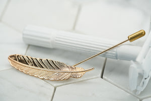 The front image of the Veder gold plated lapel pin by Dear Martian. the lapel pin has a detailed feather shape.