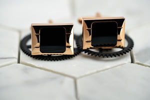 A front view image of the Carre rose gold cufflinks for men, which lay against two black cogs.