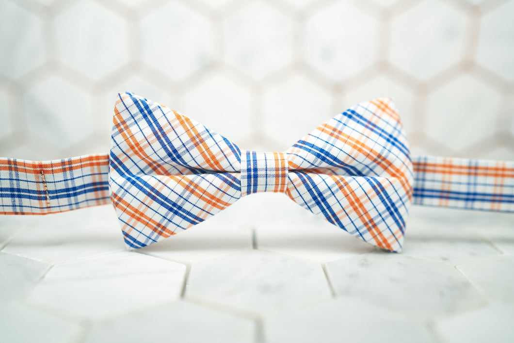 An image of the orange madras patterned bow tie sitting against a hexagon tiled background.