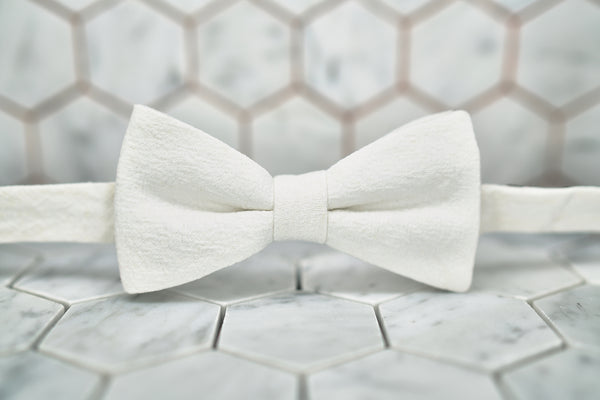 A front view of the DM Al Pacino white linen bow tie against a hexagon background.