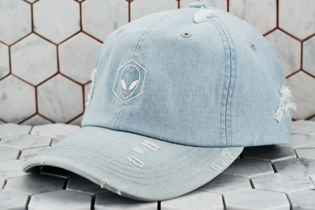 The front view of the distressed denim blue Dear Martian hat, which has a white embroidered hexagon logo.