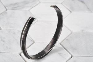 An image of a vintage steel cuff bracelet for men standing up so you see the sharp ends of the bracelet.