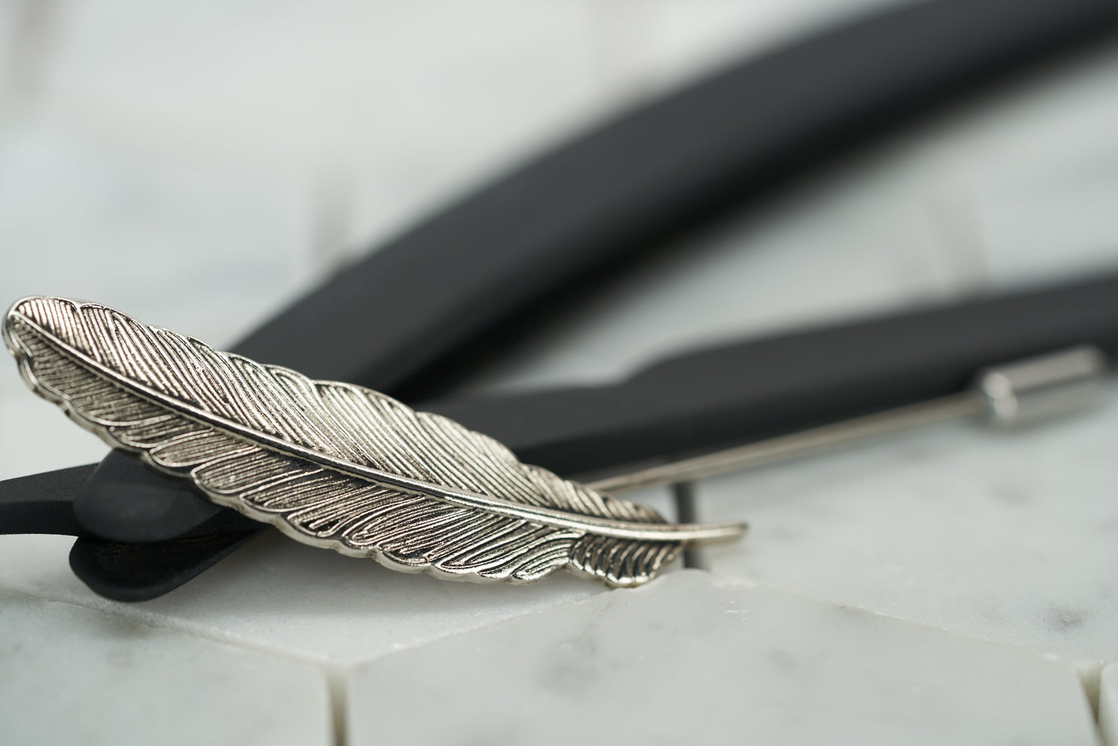 A front image of the antique silver feather lapel pin by Dear Martian, Brooklyn.