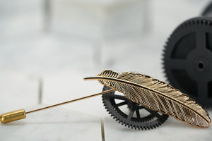 An image of a vintage gold feather lapel pin handmade by Dear Martian, Brooklyn; the suit pin sits against vintage black cogs.