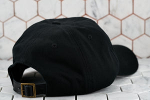 A back view of the raw black cotton twill hat by Dear Martian, which shows the antique brass buckle closure.