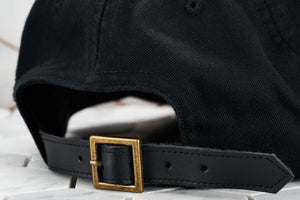 An up close image of the pointed leather adjustable strap back for the Dear Martian black hat, which features a vintage brass belt buckle.