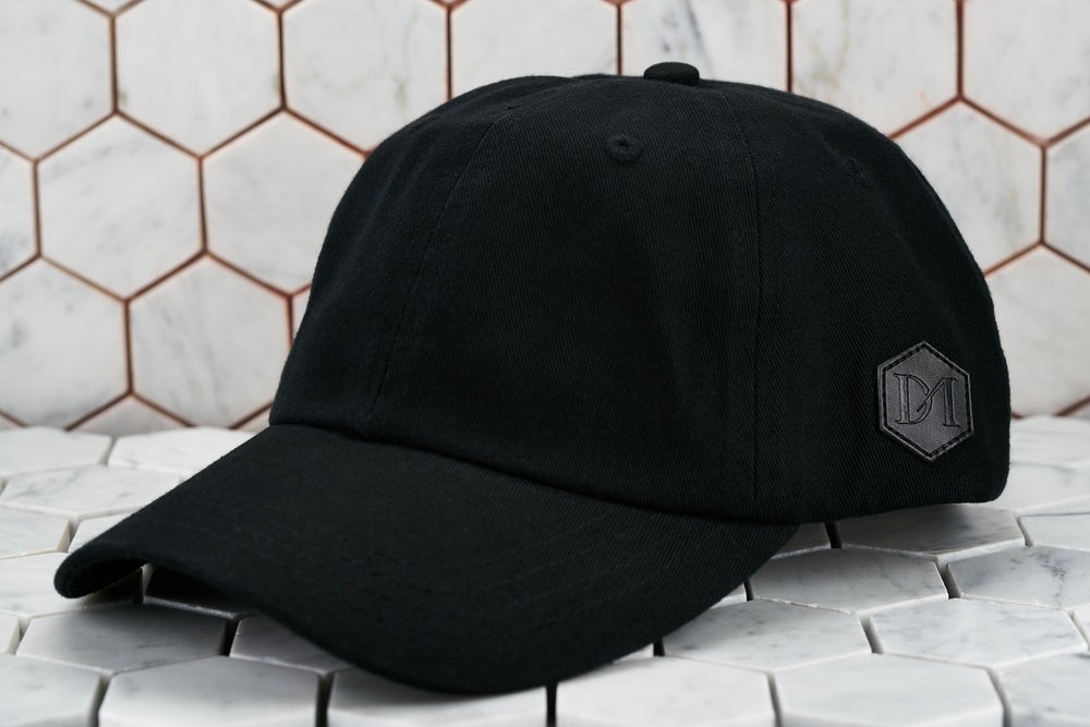 A front image of the Dear Martian, Brooklyn all black hat, which features a hexagon DM logo patch on the side.