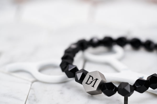 A close up photo of the Black Soul faceted 8mm onyx beaded bracelet for men. This bracelet features a steel Dear Martian hexagon logo bead.