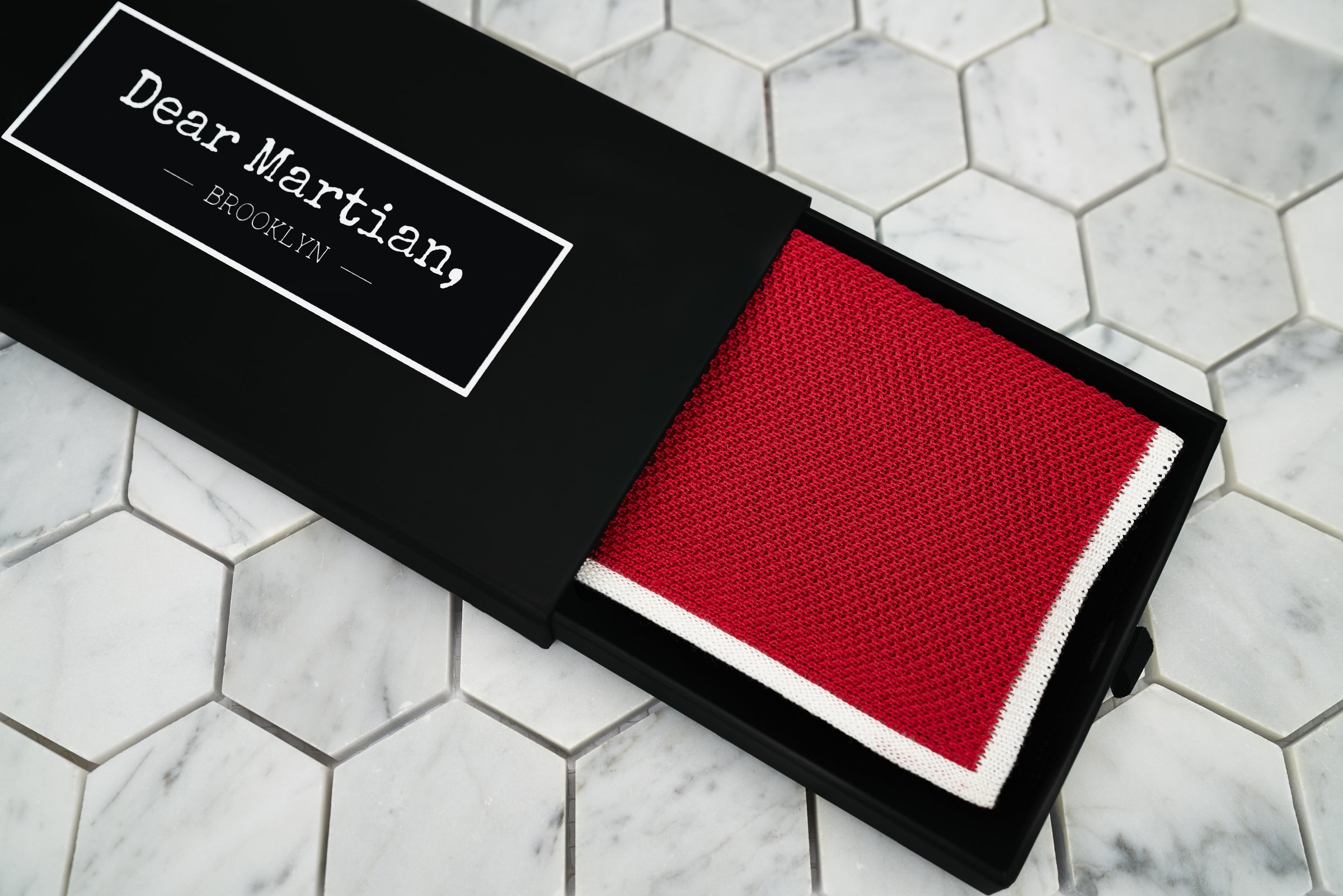 An image of the knitted red handkerchief inside the Dear Martian, Brooklyn black pull out style box.