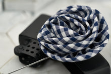 A side photo of the blue moon groomsmen boutonniere; which features a blue plaid pattern.