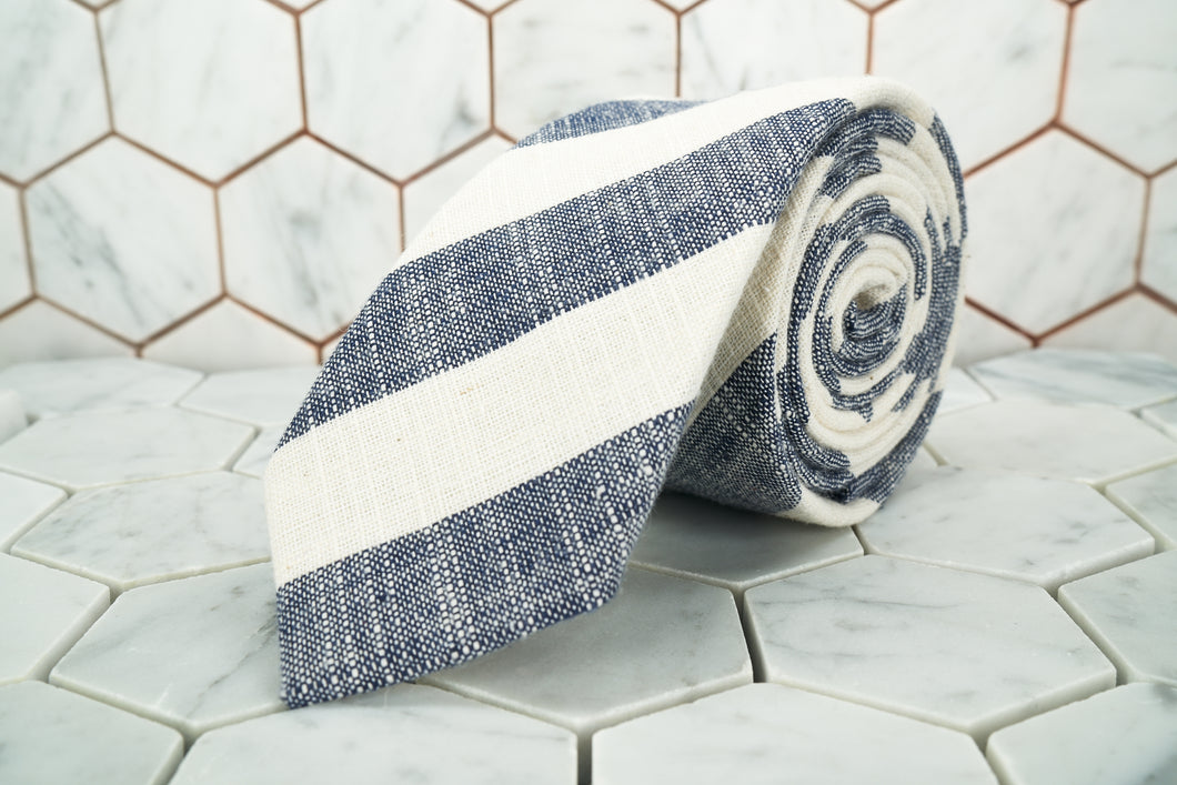 The Dear Martian grey and white striped bookie tie is rolled up  against a hexagon tiled background.