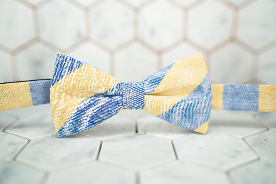 An image of Dear Martian's Bookie bow tie, which has a light yellow and blue striped pattern.