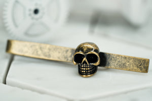 A side view image of the rustic brass skull tie clip by Dear Martian, Brooklyn.