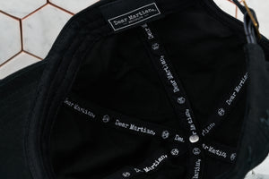 A detailed photo of the inside view of the black hat, which shows the Dear Martian, Brooklyn logo and inner taping.