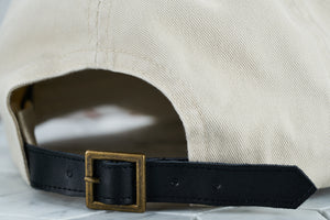 A detailed shot of the Dear Martian, optional pointed leather strap, which features a brass belt buckle.