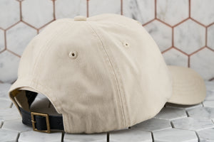 The back image of the minimal hex hat by Dear Martian in a khaki color. The back shows the belt buckle genuine leather strapback.