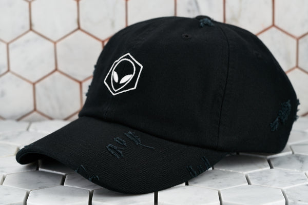 A front product image of the distressed black baseball cap with a white embroidered alien; made by Dear Martian, Brooklyn.