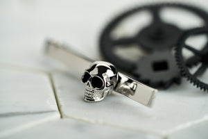 An image of Dear Martian's silver plated men's tie bar that features a skull with enamel eyes. The tie bar is facing to the left with black spray painted vintage cogs.