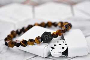 An image of the tiger eye stone bead bracelet by Dear Martian sitting on top of a white zippo lighter.