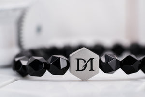 A detailed image of the steel DM logo bead strung with energy onyx stone beads to form a beautiful accessory bracelet.