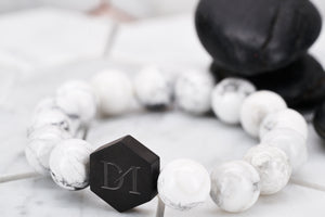 A side view image of the Jon Snow white bead bracelet by Dear Martian Brooklyn. In the background lies two black rocks for contrast of the white howlite stone.