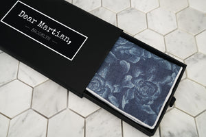 A birds eye view image of the denim blue pocket square, which is lying inside the Dear Martian black box.