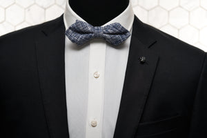 A photo of a Dear Martian mannequin wearing our men's accessories; a vintage gold Vie skull lapel pin and the navy lined pratt bow tie.